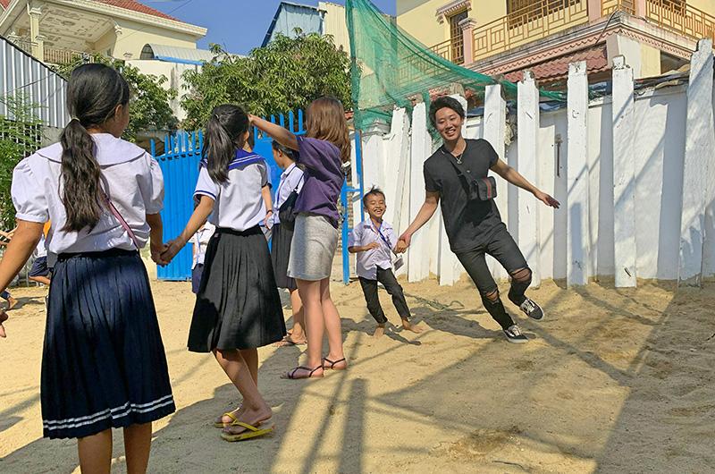 カンボジア・愛センター(経済的事情から学校に通えないカンボジアの子供たちを支援するフリースクール)の子供たちと一緒に遊ぶ経済学部の3・4年次生たちの写真
